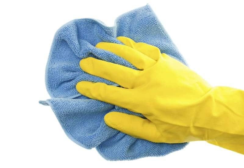 How to Clean Microfiber Cloths The Right Way -- Hand wearing rubber cleaning glove and using a microfiber cloth
