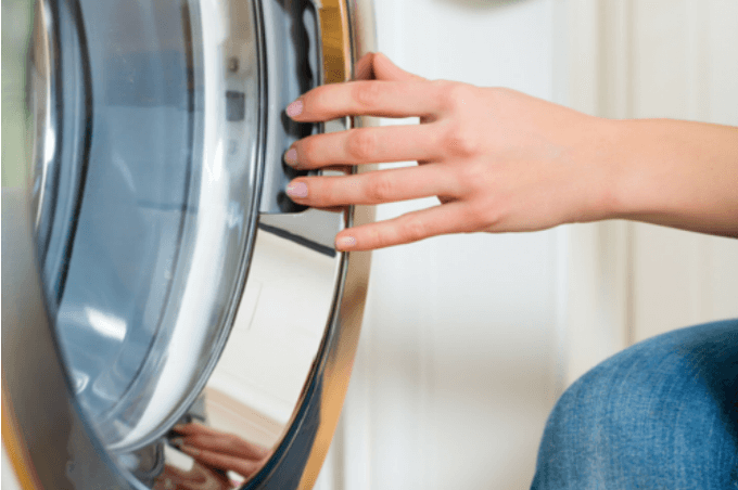 Woman opening dryer door