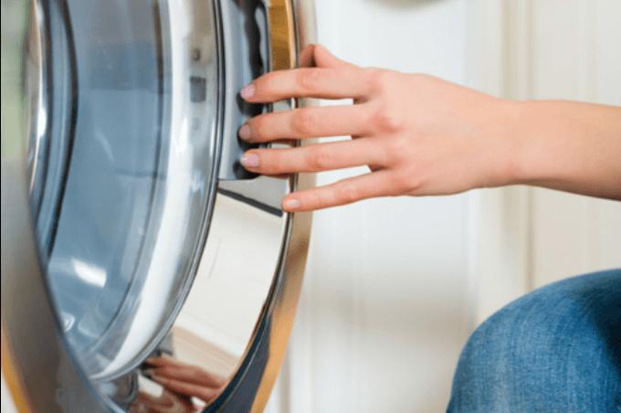 Woman opening dryer door