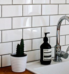 How to Clean Grout Naturally - White subway tile with gray grout over kitchen sink