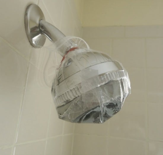 Fill a plastic bag with water and vinegar and attach it to your shower head