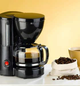 How to Clean a Coffee Maker - Machine and bag of coffee beans on counter with coffee cup
