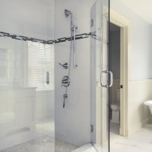 Tile and glass shower next to a claw foot tub in farmhouse style bathroom