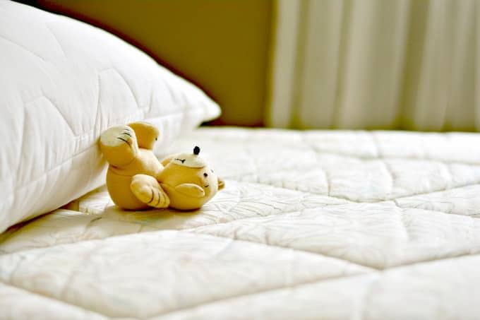 How to Clean a Mattress - A bare mattress with a pillow and teddy on it
