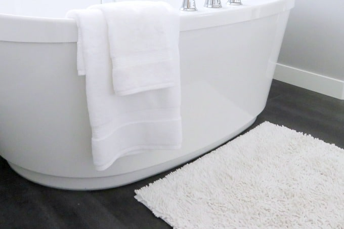 White Plush Rug In Front Of A Bathtub