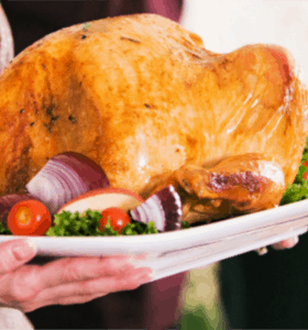 How to Roast a Moist Turkey - Woman carrying a perfect turkey on platter