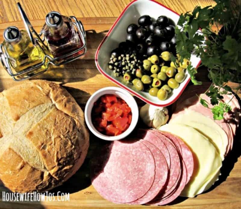 Round loaf of bread, deli meats and olives on a wood cutting board