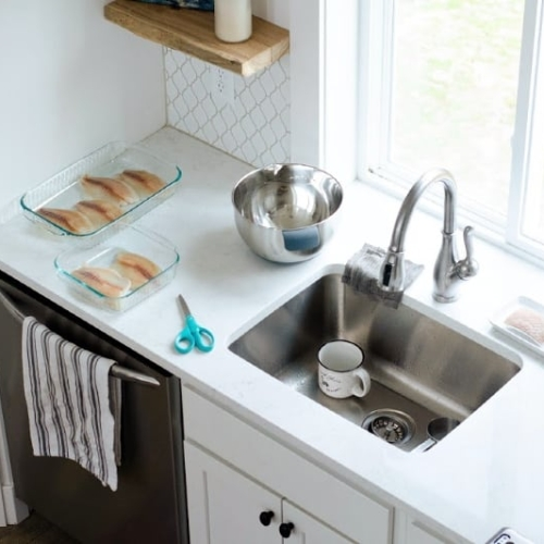 Kitchen sink and surrounding counters with loaves of bread