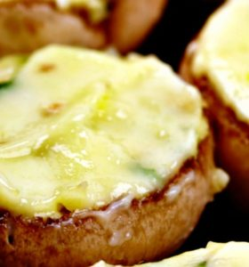 Three Cheese and Crab Stuffed Mushrooms baked until the cheese is golden and served on a tray as an appetizer