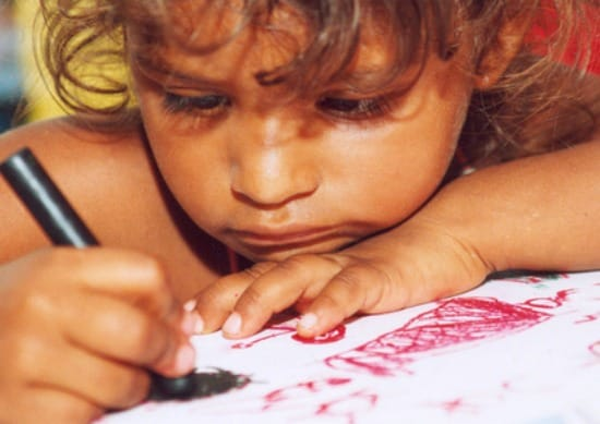 Young girl coloring a picture with a sad look on her face