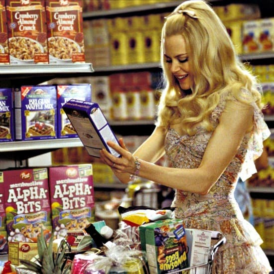 Movie still from Stepford Wives as Nicole Kidman stares at a box of cereal with great delight
