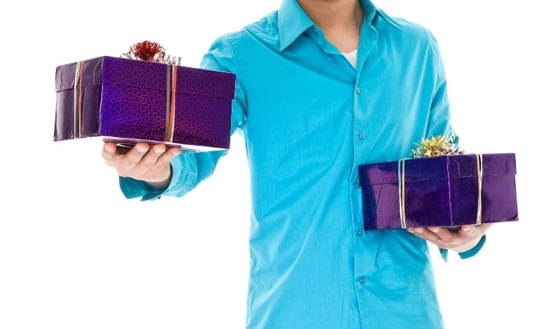 Man holding a beautifully wrapped gift in each hand