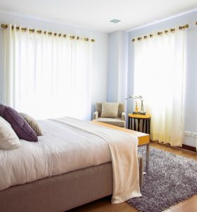 Modern bedroom with well-made bed and curtains filtering sunlight