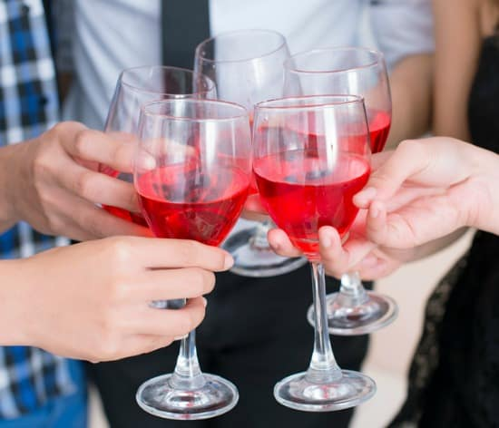 Closeup of people toasting with full wine glasses