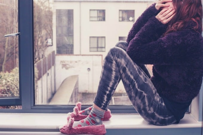 Stressed woman in purple pajamas and slippers sitting on windowsill covering her face