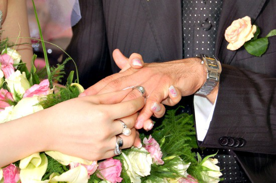Bride putting wedding ring on groom's finger