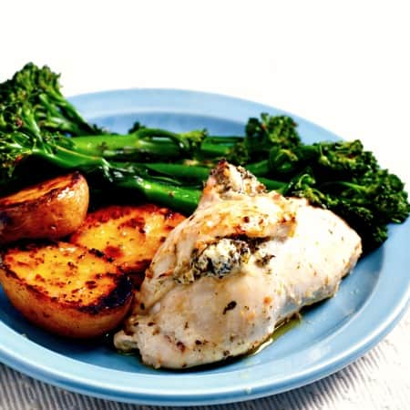 Chicken and Spinach Roulade on a blue plate with roasted sweet potato and broccolini