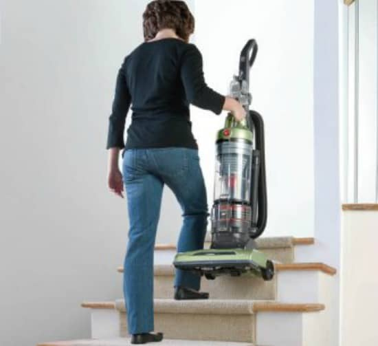 Woman carrying upright vacuum on stairs