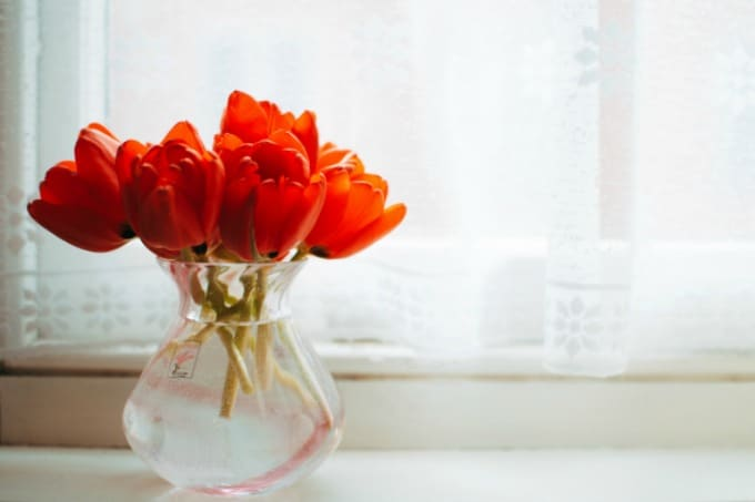 Flowers in a glass vase on a windowsill with sheer curtains in the background showing how to clean curtains