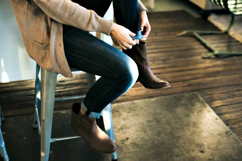 How to Get Salt Stains off Shoes - Woman sitting on stool to put on short brown boots