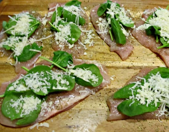 Topping seasoned chicken with layers of spinach and cheese