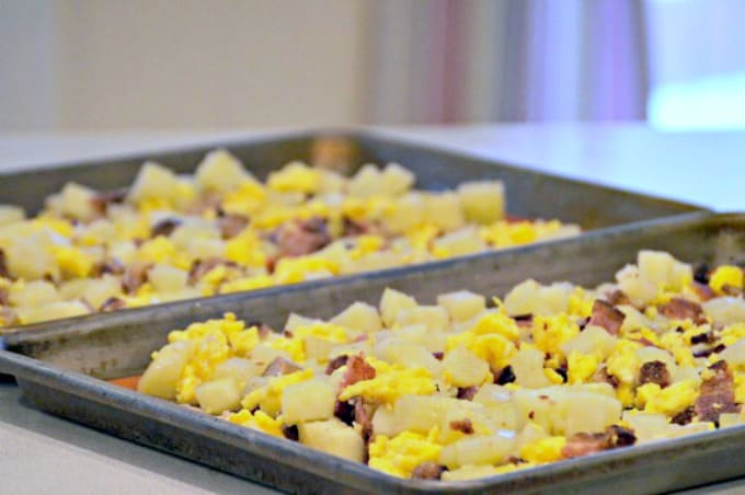 Potatoes, bacon, sausage, and scrambled eggs combined on a baking sheet
