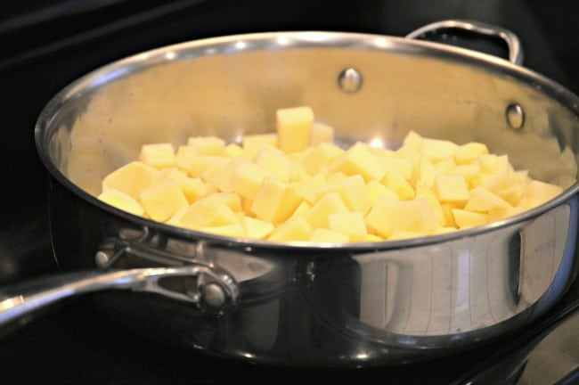 Peeled and chopped potatoes cooking in a steel skillet on the stove