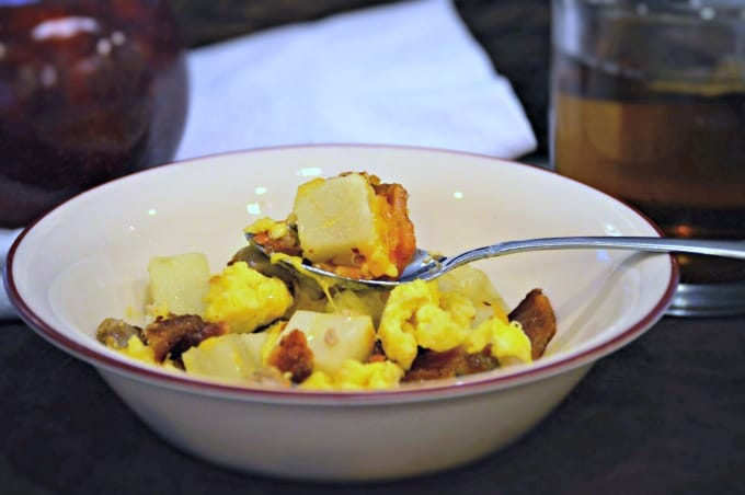 A bowl of Meal-prep Hot Breakfast Bowls recipe featuring scrambled eggs, potatoes, bacon, sausage, and cheddar cheese