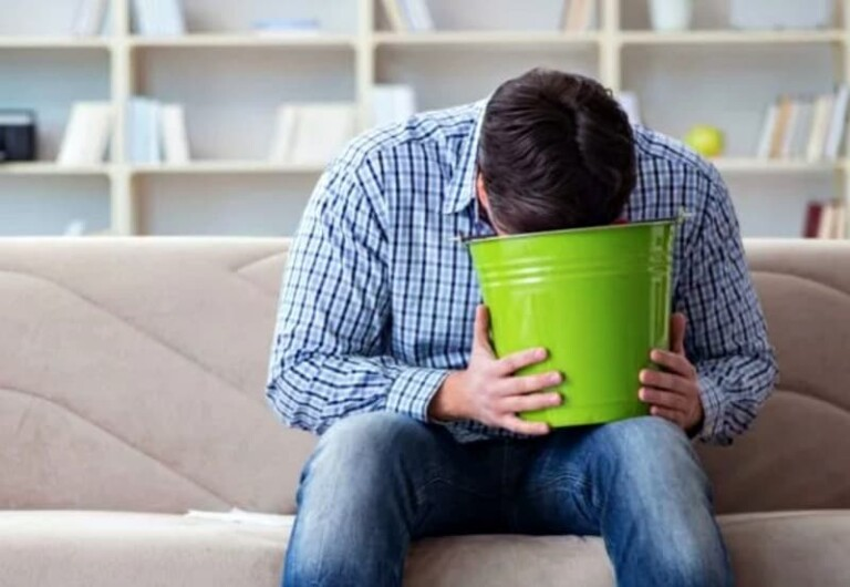 How to Clean Vomit - Man with stomach flu vomiting into bucket