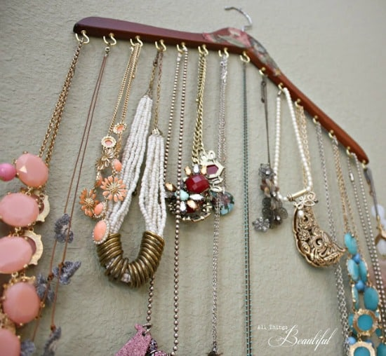 Wood hanger with small cup hooks attached and necklaces hanging from them