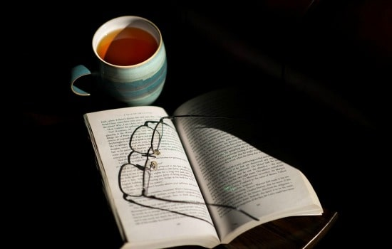 A cup of tea sitting next to a book with a pair of reading glasses on top of it