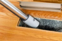 Using vacuum cleaner to remove debris inside home air ducts