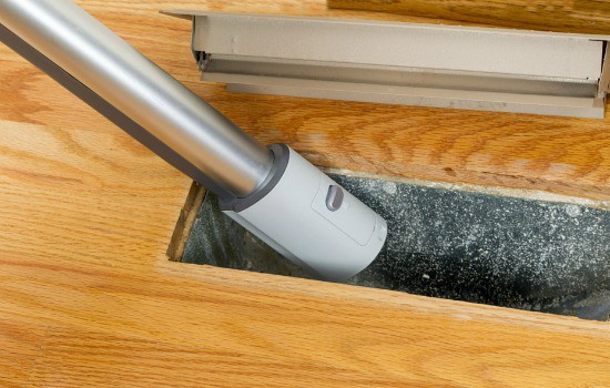 How to Clean Your Own Air Ducts - Vacuum hose inserted into a floor register demonstrating how to clean your air ducts