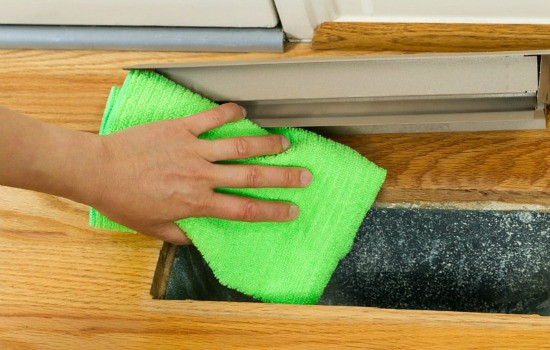 How to Clean Your Own Air Ducts - A person wiping the inside of their air ducts with a microfiber cloth