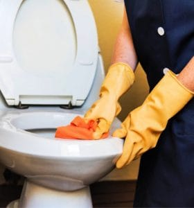 10 Professional Home Cleaning Hacks - House cleaner scrubbing toilet