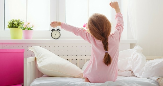 Picture of a little girl sitting on her bed and stretching