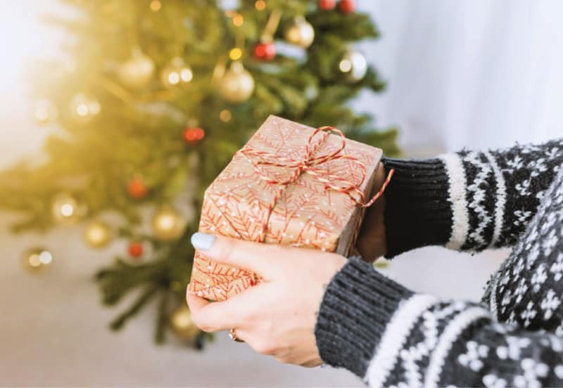 How to Avoid Holiday Stress - Woman holding wrapped Christmas gift in front of decorated tree