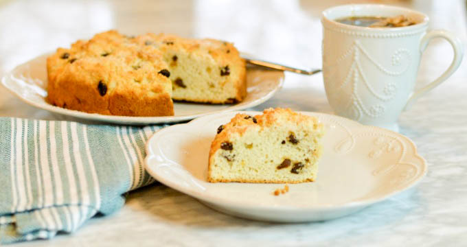 A platter of Irish Tea Cake with one slice on a small serving plate next to a cup of tea