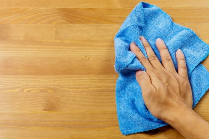 How to Reduce Dust in Your Home by using a microfiber cloth to wipe surfaces