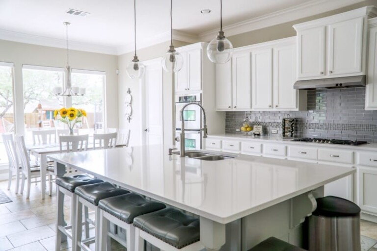 Kitchen Spring Cleaning Checklist - Clean modern kitchen with white cupboards and granite countertop