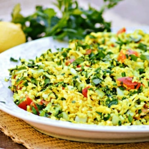 Tabbouleh Style Turmeric Cauliflower Salad on a serving platter with lemon and herbs in the background