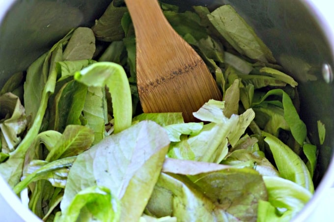 Torn lettuce leaves being stirred into cooking pot with wooden spoon