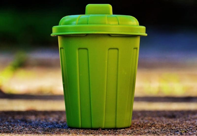 How to Clean Trash Cans - Green can on sidewalk
