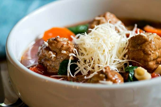 Meatball soup garnished with shredded parmesan cheese