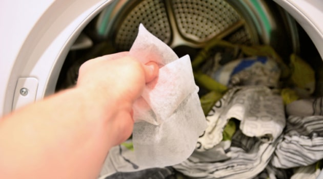 Uses for Used Dryer Sheets - Hand putting one into dryer