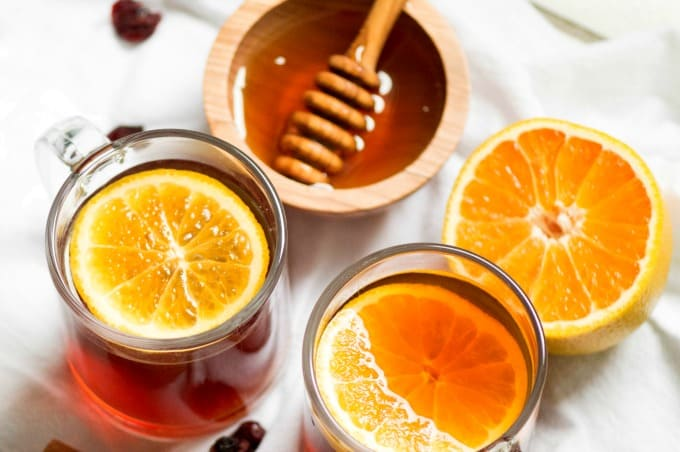 Crockpot Cranberry Citrus Cinnamon Tea in cups with floating orange slices
