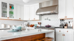 Modern white kitchen with stainless steel range hood and granite countertops