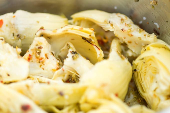 artichoke hearts and seasonings in pan