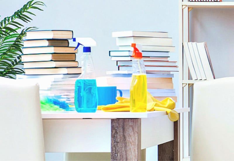 How to Create a Cleaning Schedule that Works - Books and cleaning products on a white table