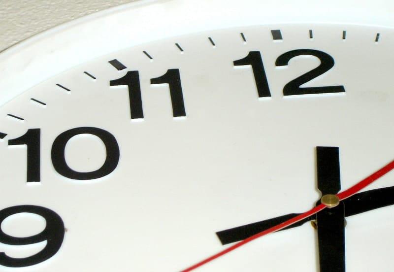 Closeup of black clock hands on a white clock